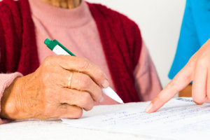 old woman writing on the paper